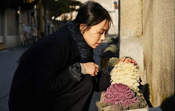 "Actress, Kim Min-hee, admiring white and purple plants in the film, ""On the Beach at Night Alone""."