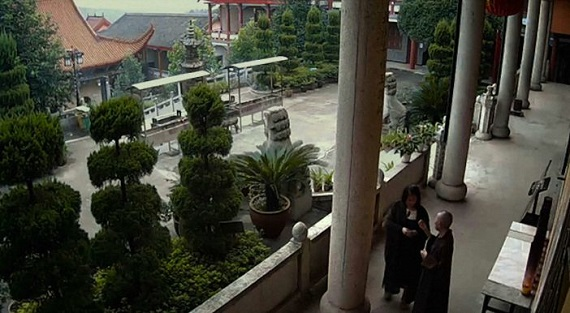A bird's eye view of a temple beside other temples. There are many groomed green plants and trees, along with two men in black robes discussing something.
