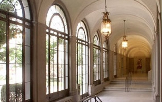 A hallway with multiple, large windows and a rounded ceiling.