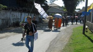 A funeral procession through town streets.