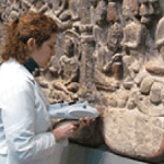 Conservaton scientist using a handheld x-ray device on a stone relief sculpture