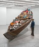 A boat with a variety of objects within. A person (blurred) approaches the artwork.