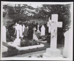 People standing in cemetery.