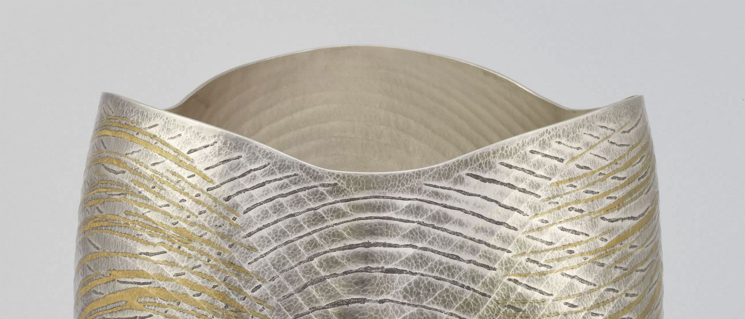 detail from Osumi Yukie's Sound of Waves, showing dark and gold wavey marks on a silver vessel with an undulating lip and wave pattern interior
