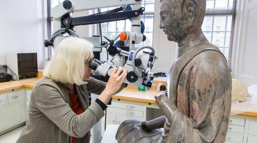 Looking at microscope at Freer Buddha