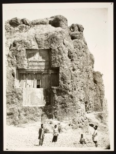 Four men stand at the foot of a cliff with tomb architecture carved into its face.
