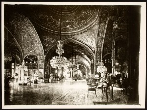 Immense palace salon with vaulted ceilings, dripping with chandeliers and ornament.