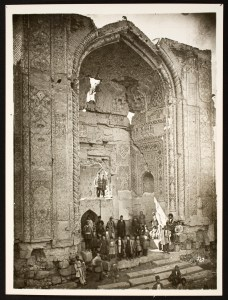 People gathered around the ruins of a large entrance portal.