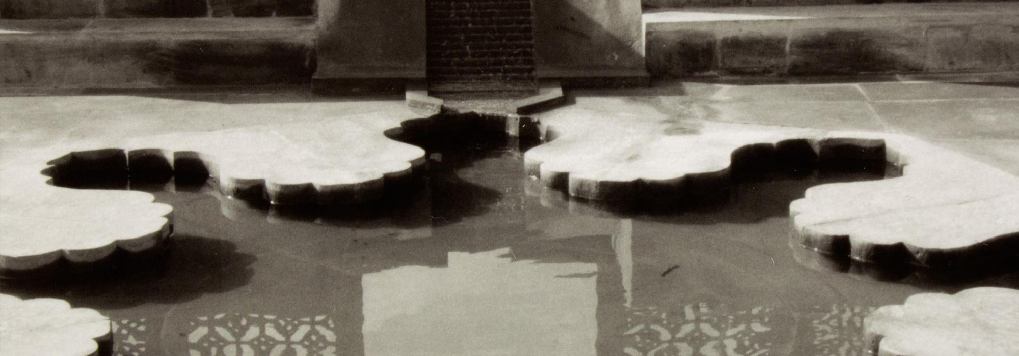 Black and white photograph of a rosette shaped reflecting pool.