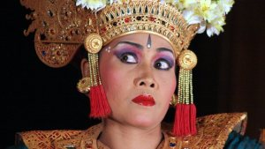 A performer wearing a gold headdress, bright makeup, and a dramatic expression.
