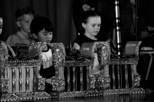 Black and white photo of young children playing in a gamelan concert.
