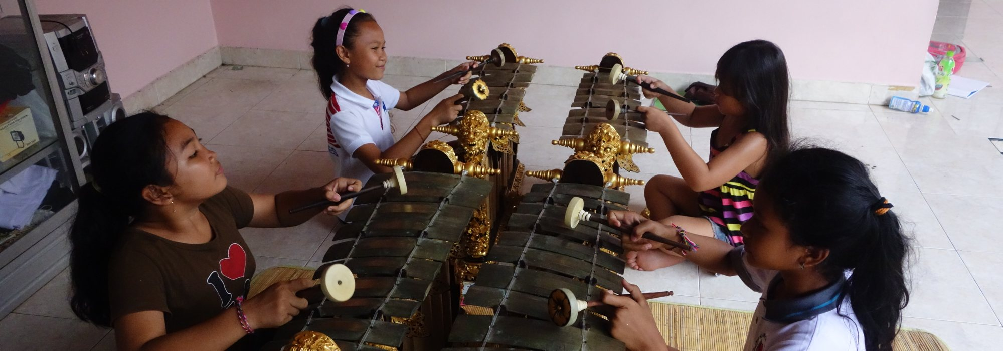 Four young girls playing gendèr metallophones.