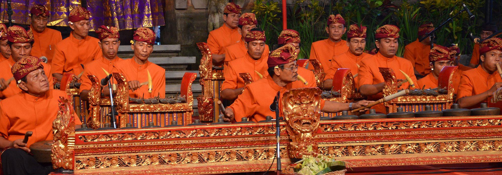 A dozen or so gamelan players wearing bright orange.