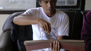 A man holding a lontar manuscript.