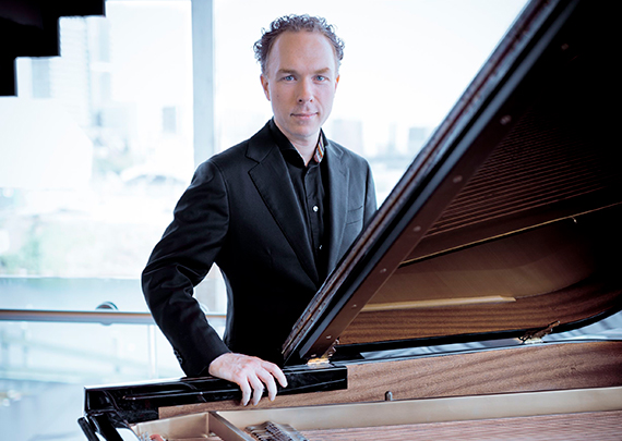 Van Raat seated at piano