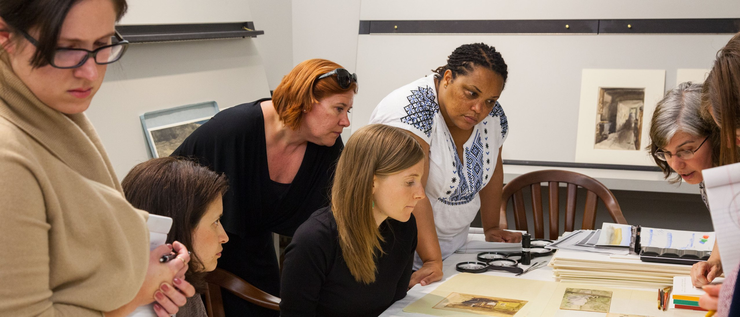 A group of women gather around as a conservator discusses an artwork laid on a table between them