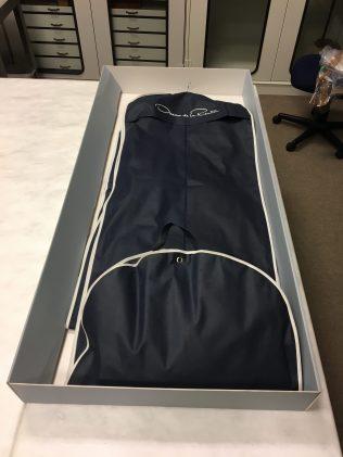 an open storage box with an Oscar de la Renta garment bag inside