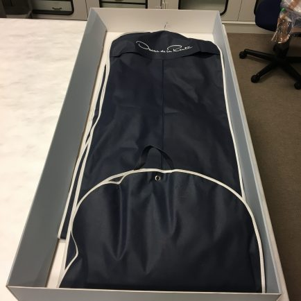 an open storage box with an Oscar de la Renta garment bag inside