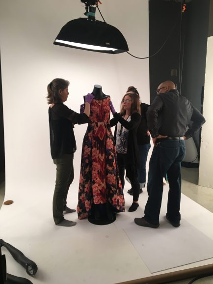 four staff members working on dressing a black fabric mannequin with a red and purple floral dress