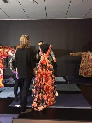 three staff members around a mannequin