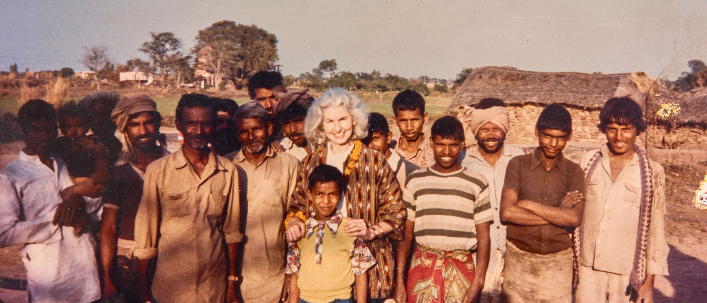 Elizabeth Moynihan posing for a photo with a group of Indian locals