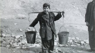 Village boy carrying two pails with a carrying pole