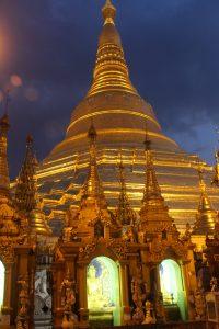 Small golden stupa spires against large golden stupa, illuminated against a dark blue sky