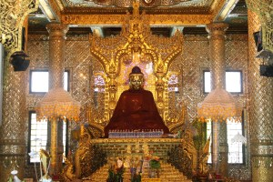 Enshrined Buddha in red robe on an ornate golden throne