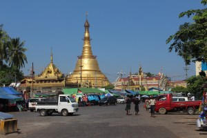 Golden stupa with people and shops in front and blue sky beyond