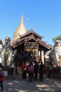 Golden-top shrine with entry pavilion and people going inside, with two mythical lion figures on either side