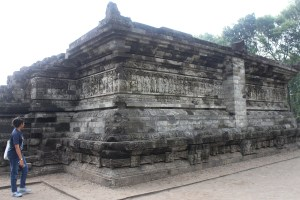 Woman walking around a large granite temple base