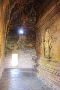Brick temple interior with Buddha against wall