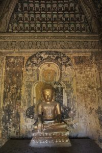 Gilt stucco seated Buddha in front of painted Buddha on a wall