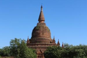 Brick stupa spire against blue sky