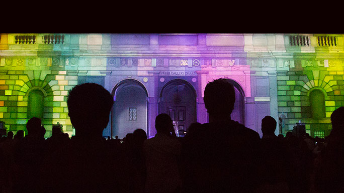 Colorful image of a projection on the front of the Freer with an audience in silhoutte in the foreground