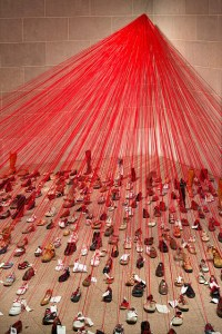 Hundreds of shoes with notes and red strings attached that all lead to a central focus