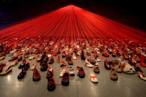 Hundreds of shoes with notes and red strings attached that all lead to a central locus above