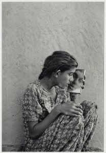 black and white photo of a girl holding a square mirror to her face