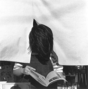 black and photo of an individual reading a magazine. there head is down and poking through a curtain, so you can't see the face