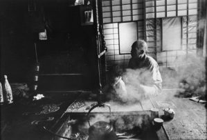 black and white photo of a man and a small child sitting near a steaming pot on the hearth, a tea set sitting ready near them