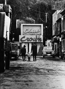 "A black and white photo of two adults walking alongside a child in front of a sign that says ""club crown"""