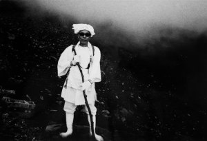 Black and white photo of a man in white clothing and gloves, holding a stick, wearing shades