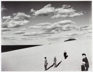 several people working on the dunes with a cloud filled sky behind them