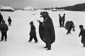 several people in the snow, one wearing a dragon mask