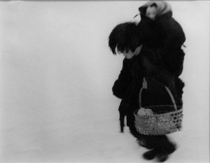 a black and white photo of a person carrying a basket