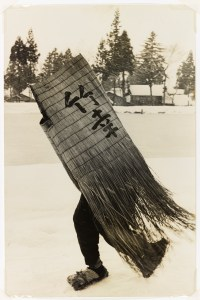 black, white, and sepia toned image of a man carrying a woven structure with Japanese calligraphy