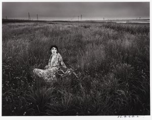 black and white photo of a person in gown sitting in a grassy field