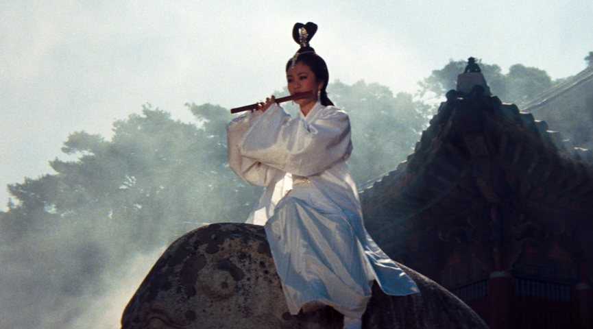 women in white gown playing a flute on top of a stone structure