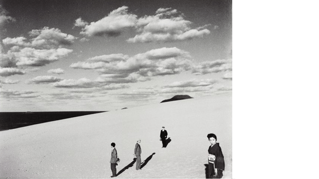 Black and white photo of people walking on a dune