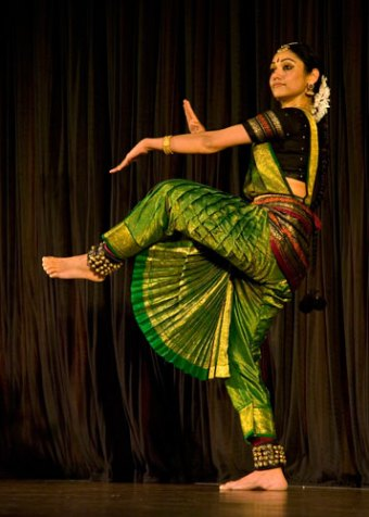 Woman performing a dance wearing traditional garments.